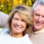 couple enjoying their cosmetic dentistry with smiles